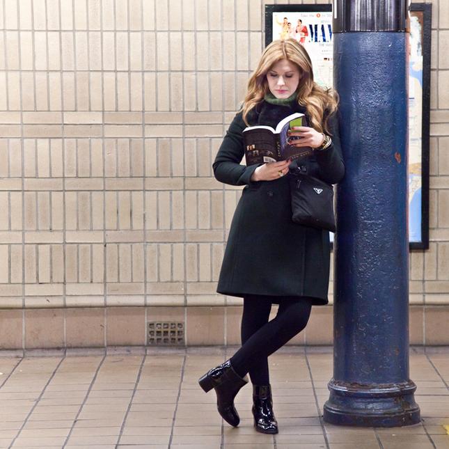 """A moça que lê """"Fallen"""", de Lauren Kate, à direita, encostada no poste."""